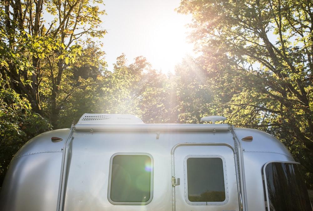 silver RV trailer near trees