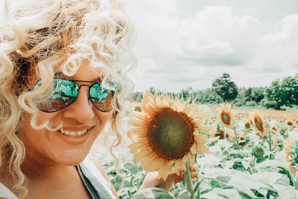 focus photography of woman holding sunflower