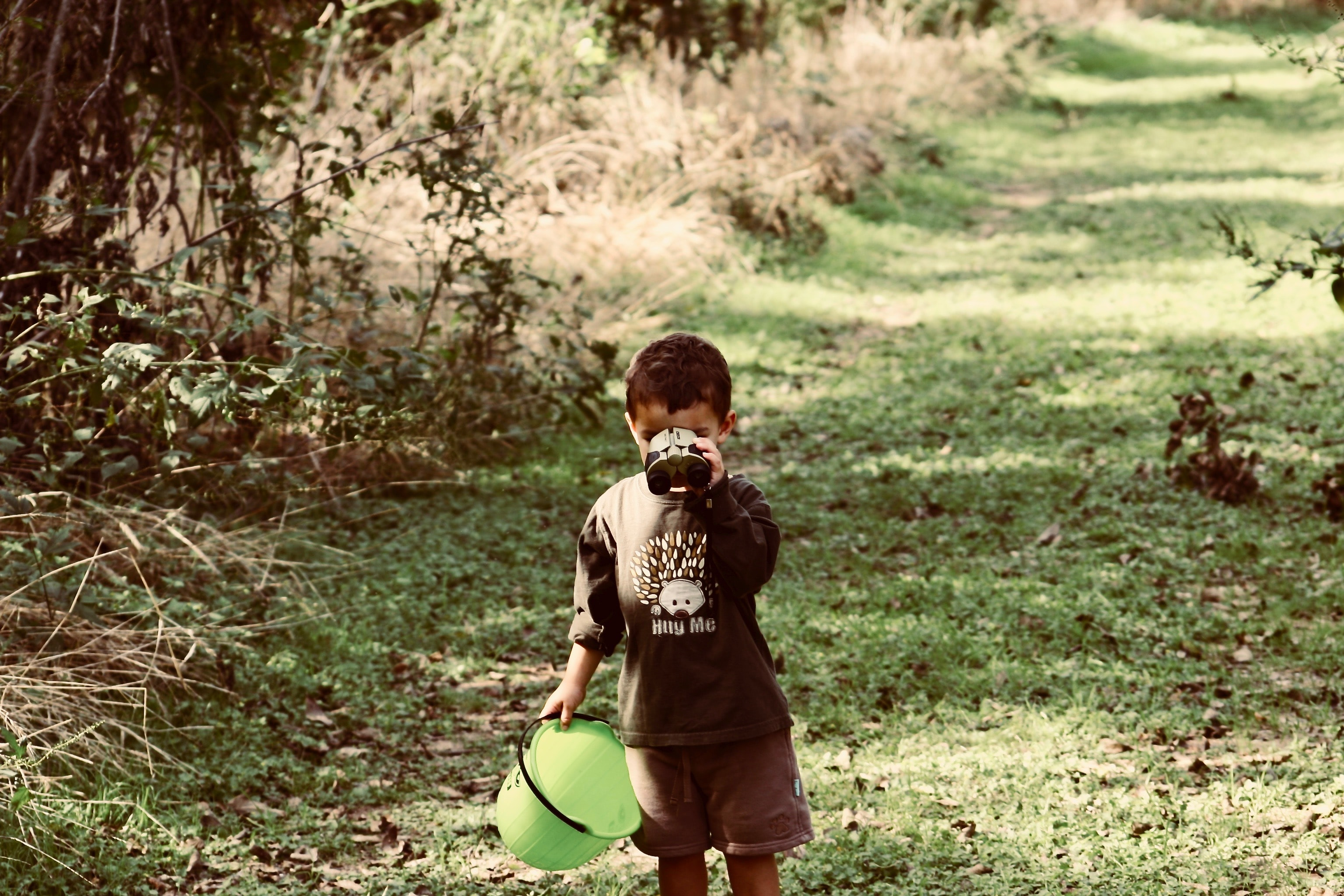 boy standing on green grass while drinking