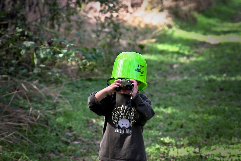 selective focus photography of boby holding binoculars