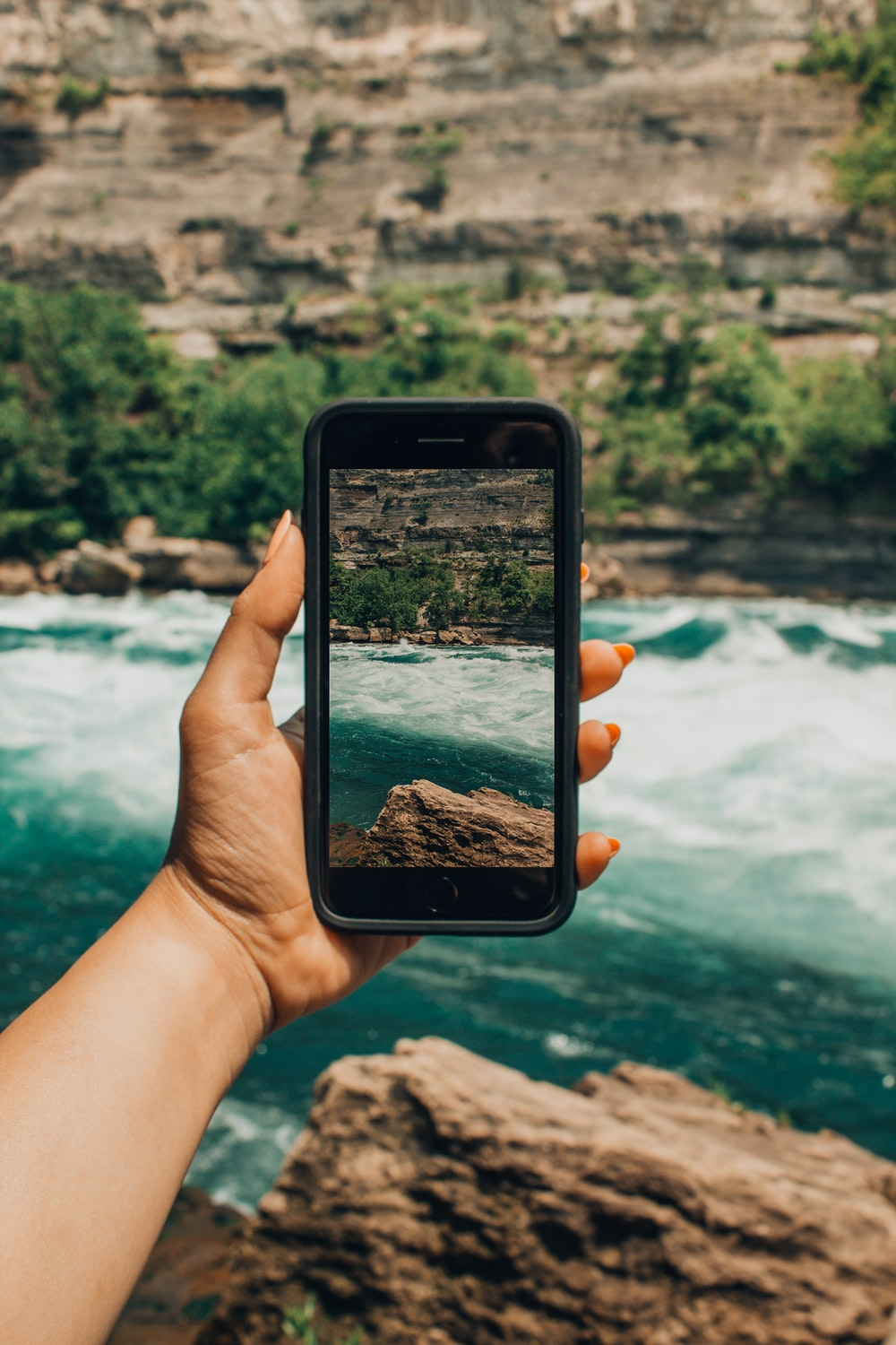 person holding black smartphone focusing body of water