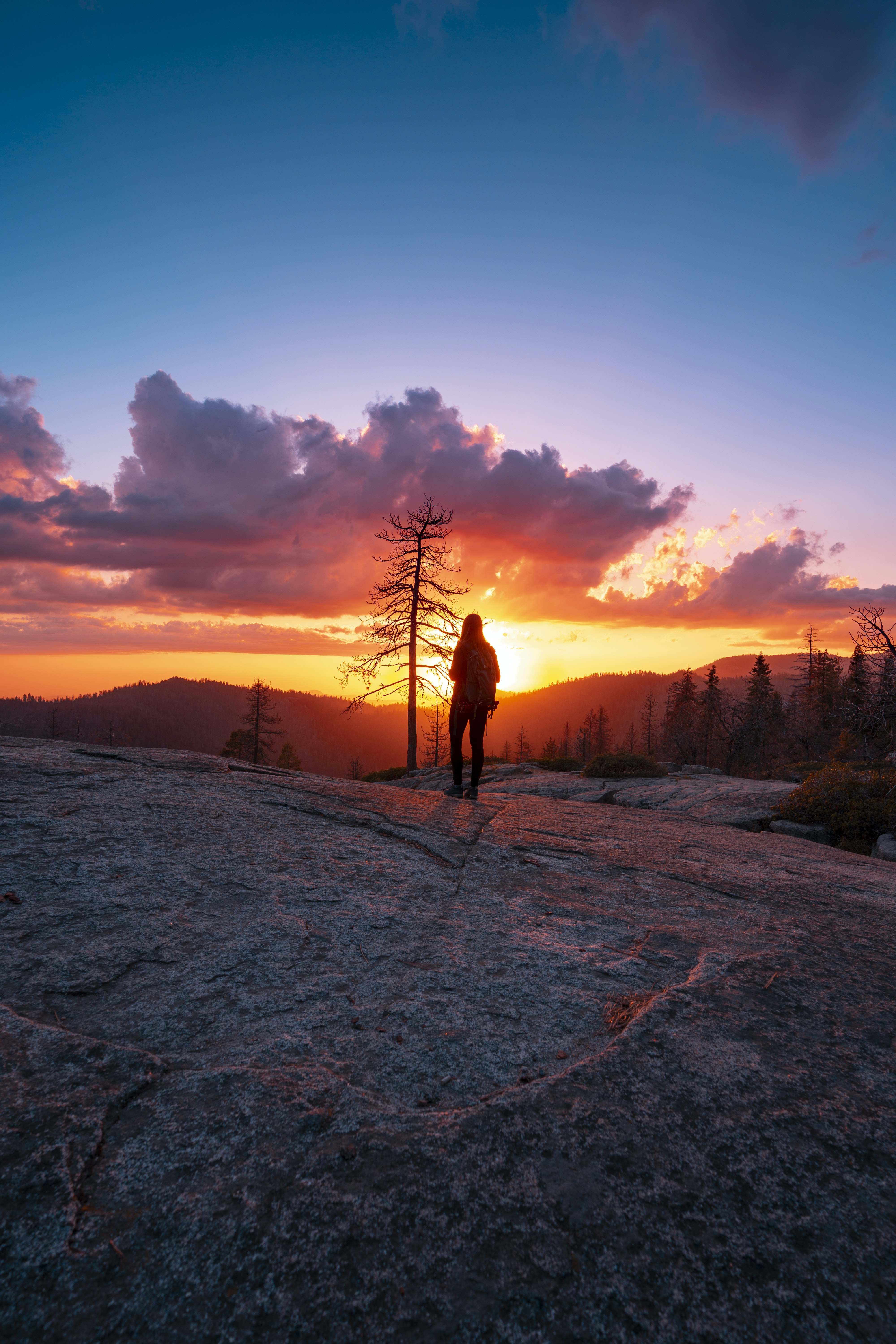 silhouette photo of woman standing on gray rock formation