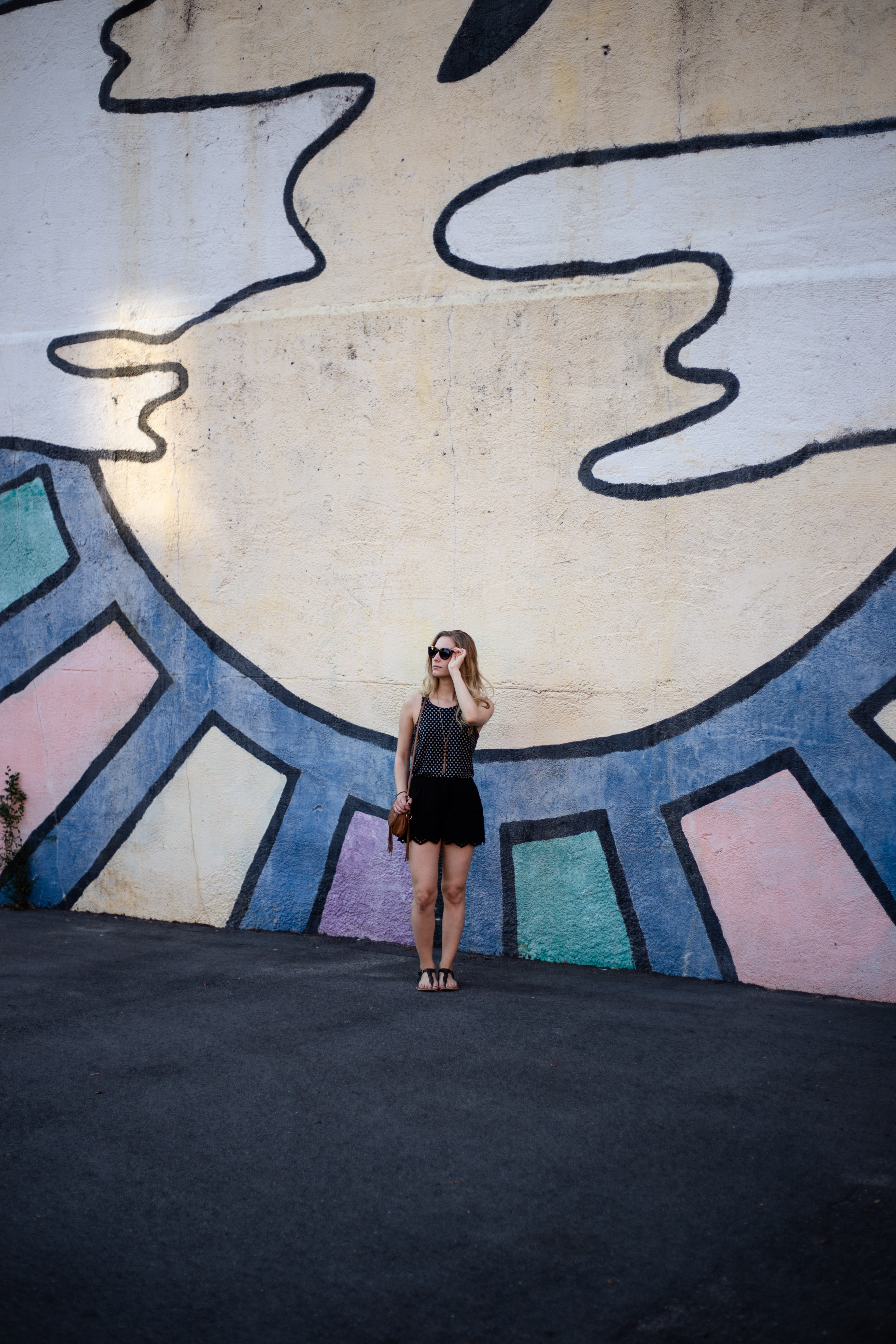 standing woman beside multicolored wall