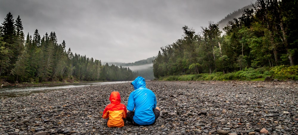 two persons sitting beside body of water