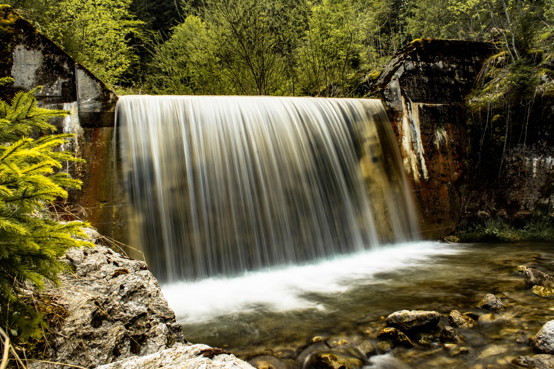 waterfalls near green trees