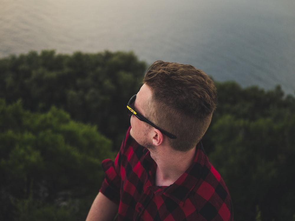 man wearing black sports sunglasses facing body of water