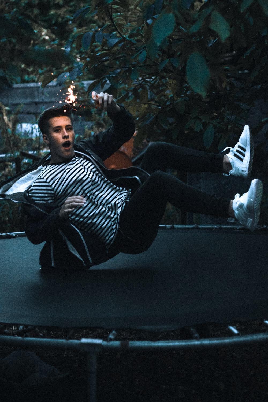 man jumping on black trampoline