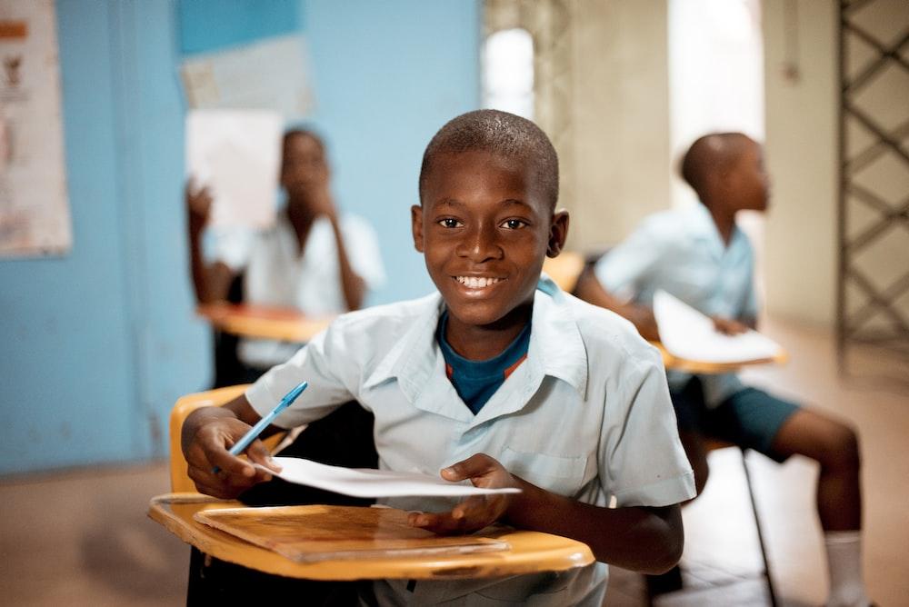 boy holding white paper