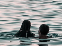 man and woman on body of water