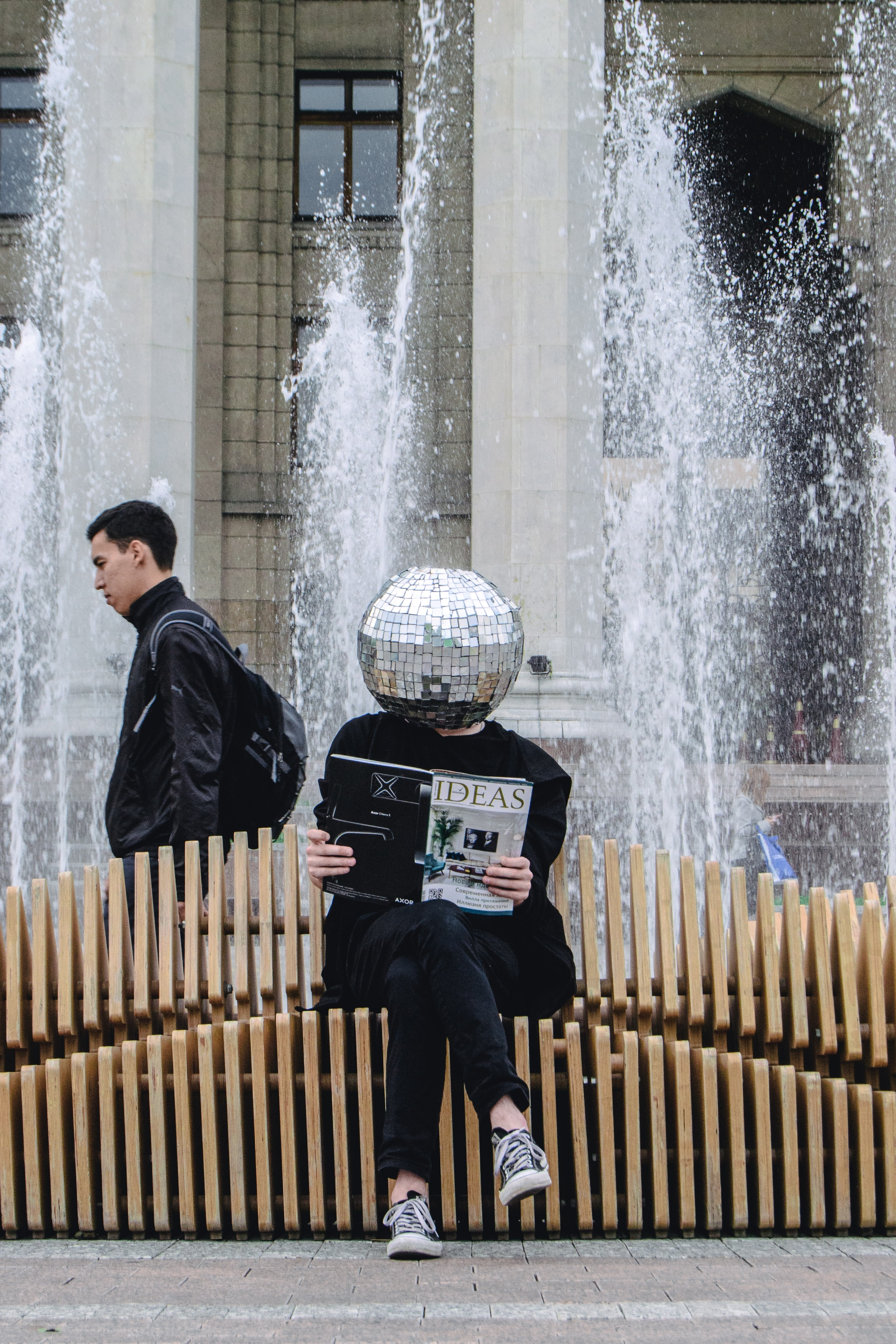 person sitting on wooden accordion bench while reading magazine at the back of water fountain
