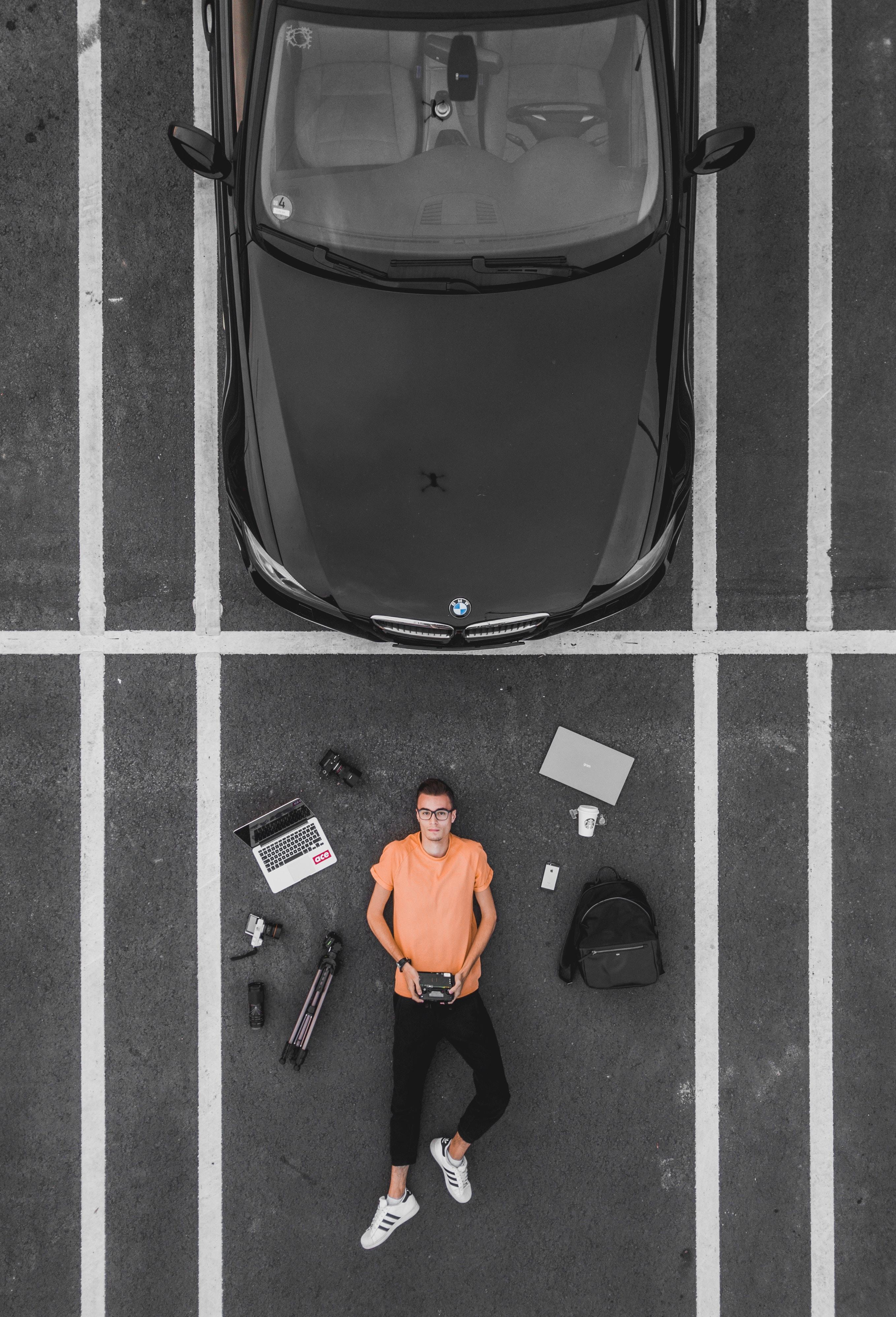 man lying on parking lot near black car
