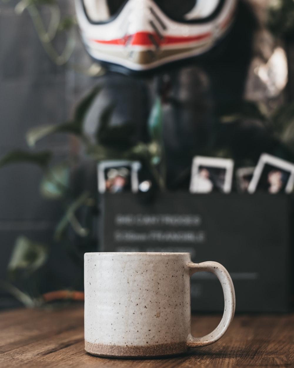 beige and gray mug on brown tabletop