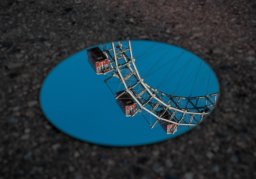 round mirror reflecting ferris wheel