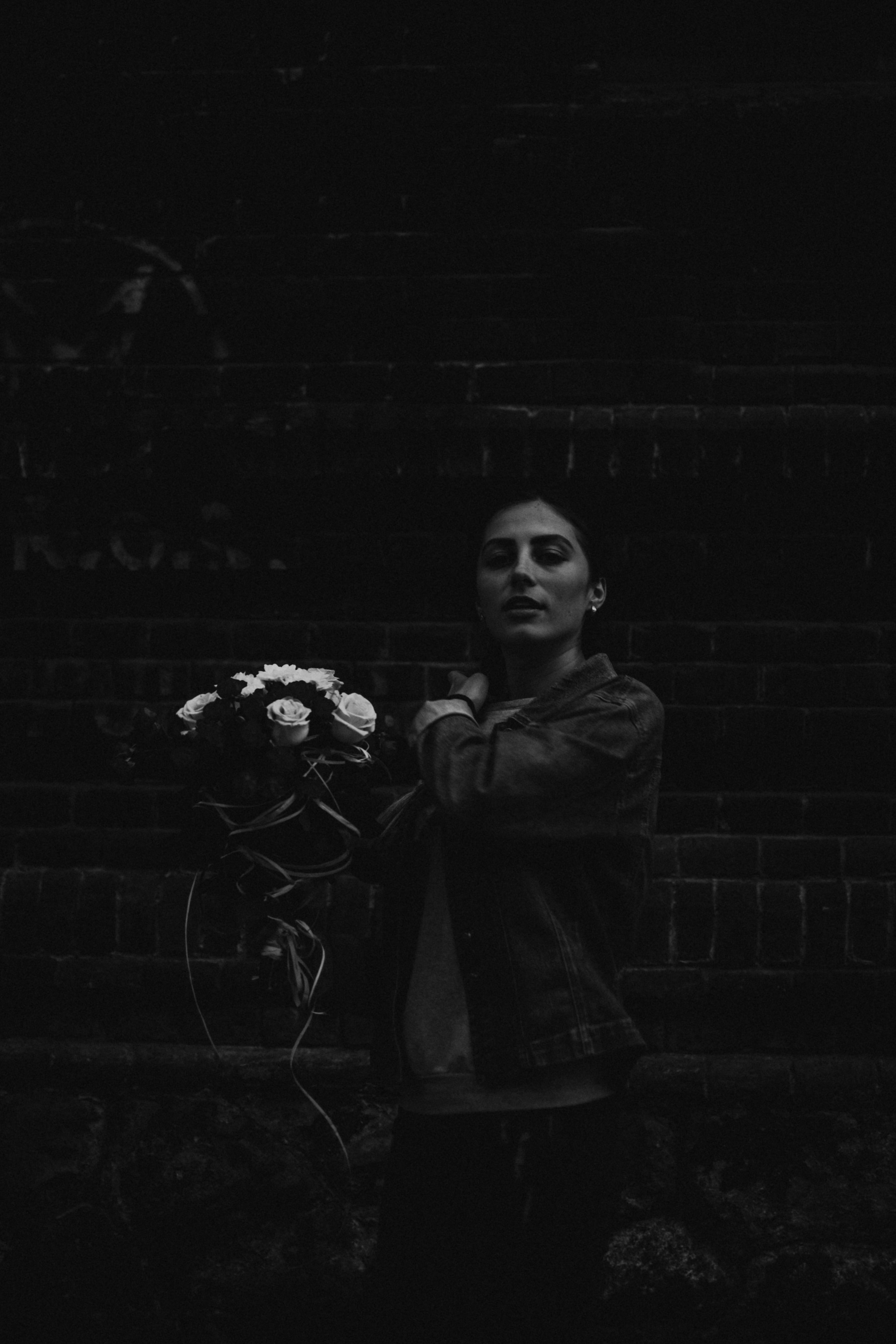 grayscale photography of woman holding flower bouquet