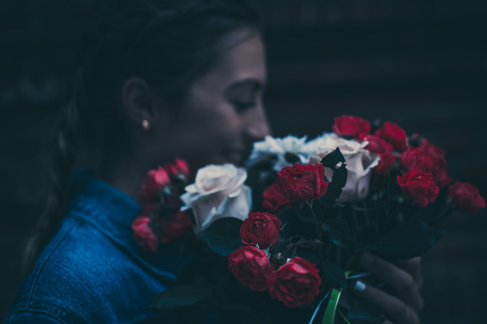 woman holding red and white rose flowers