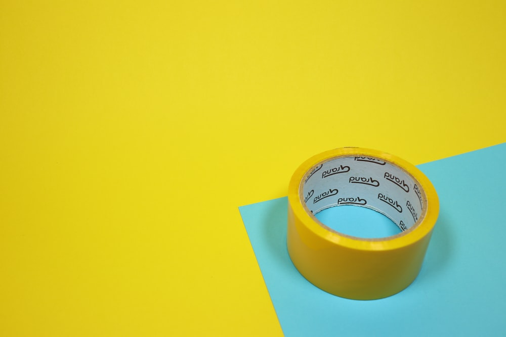 yellow duct tape on blue surface