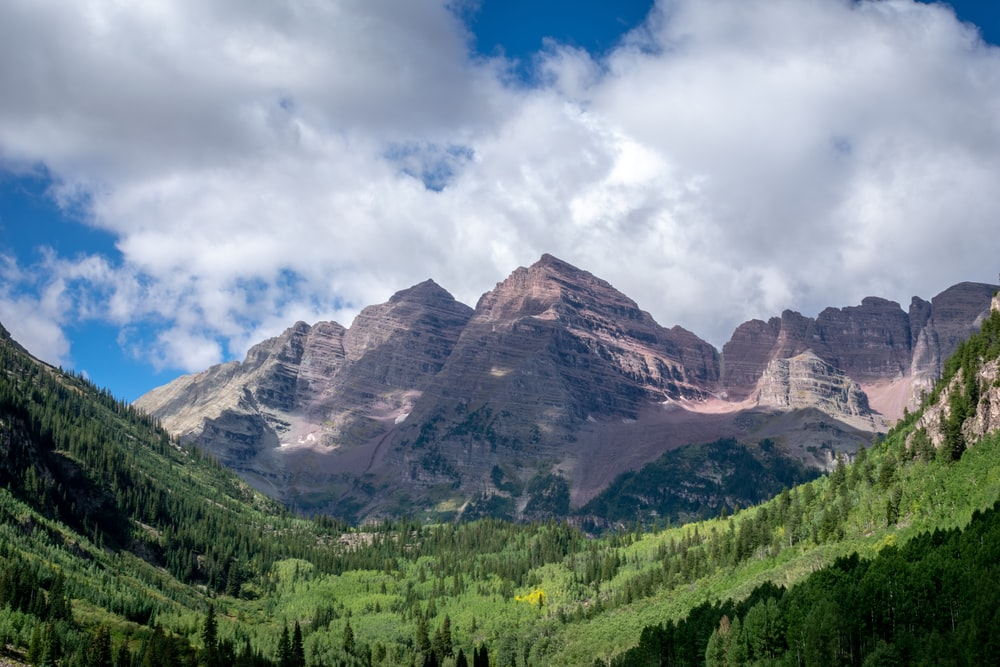 high-angle photography of mountain near field of trees