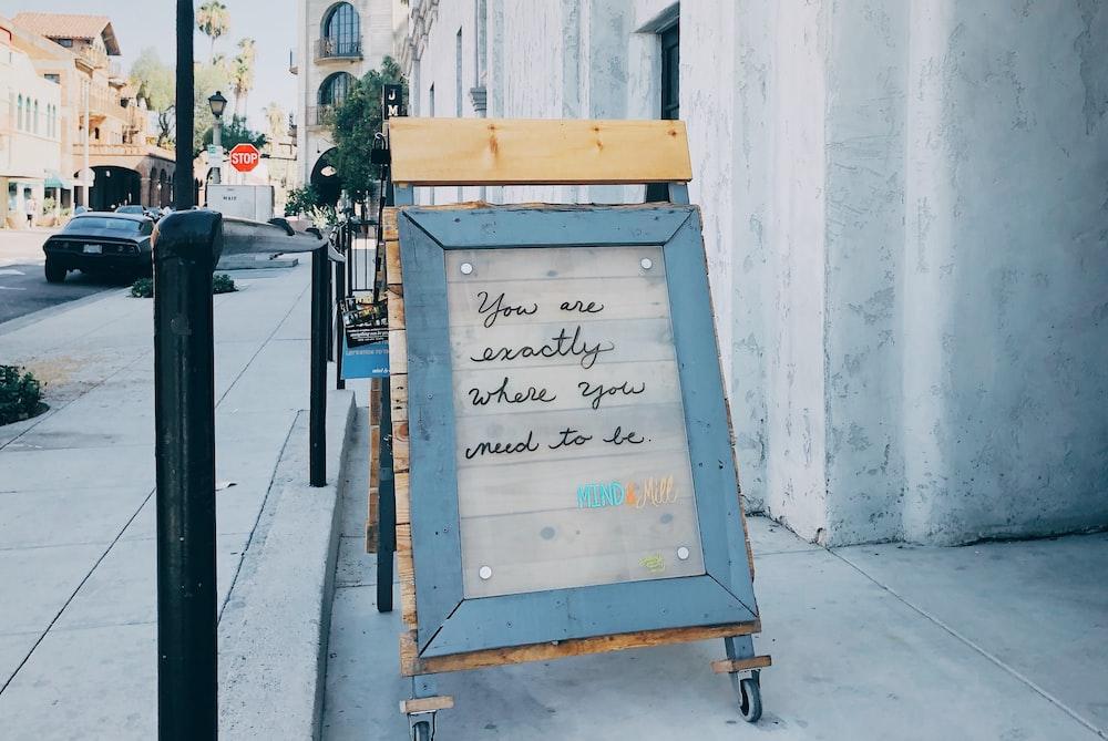 brown framed text beside street