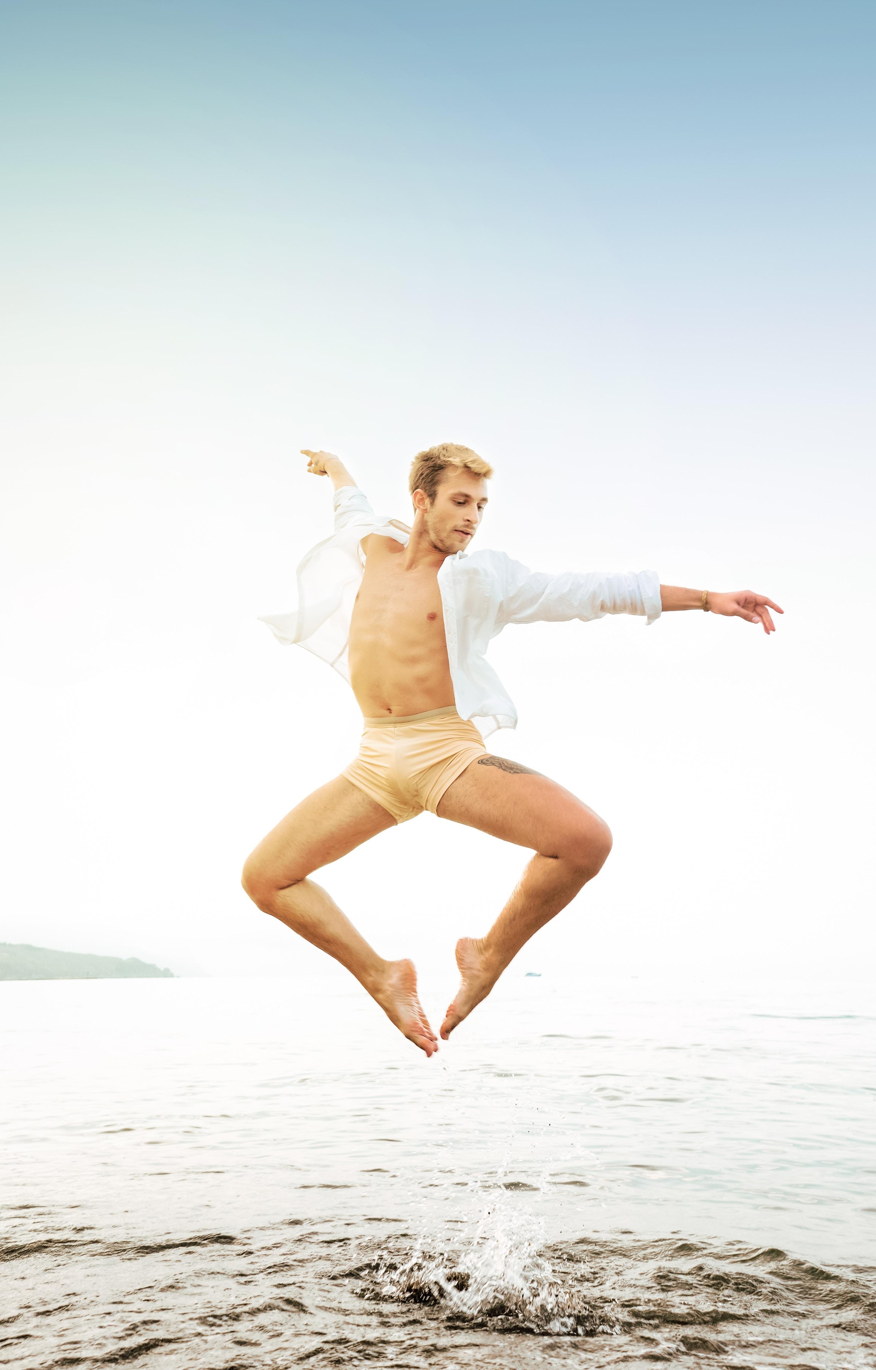man jumping near seashore