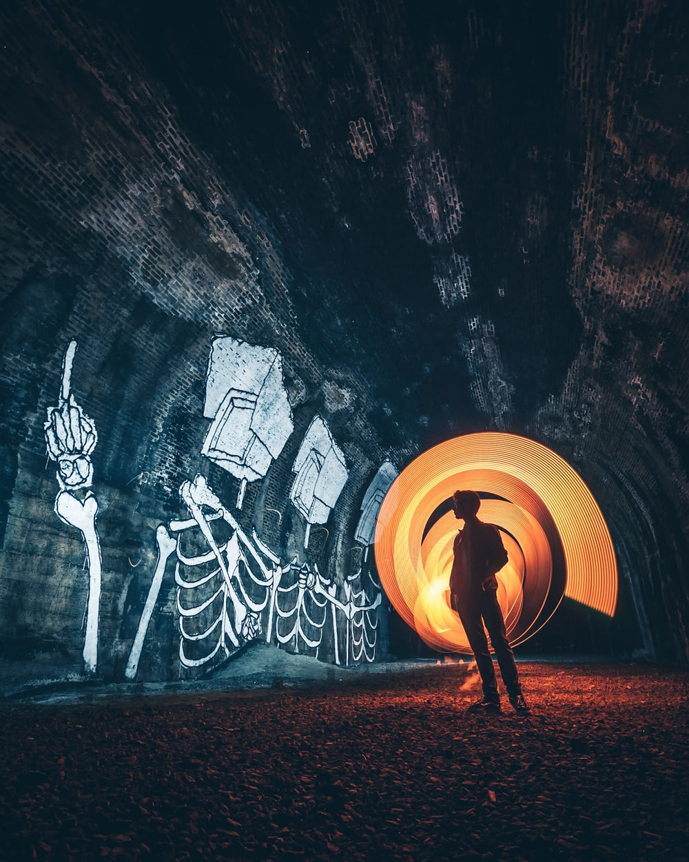 silhouette of person standing inside tunnel