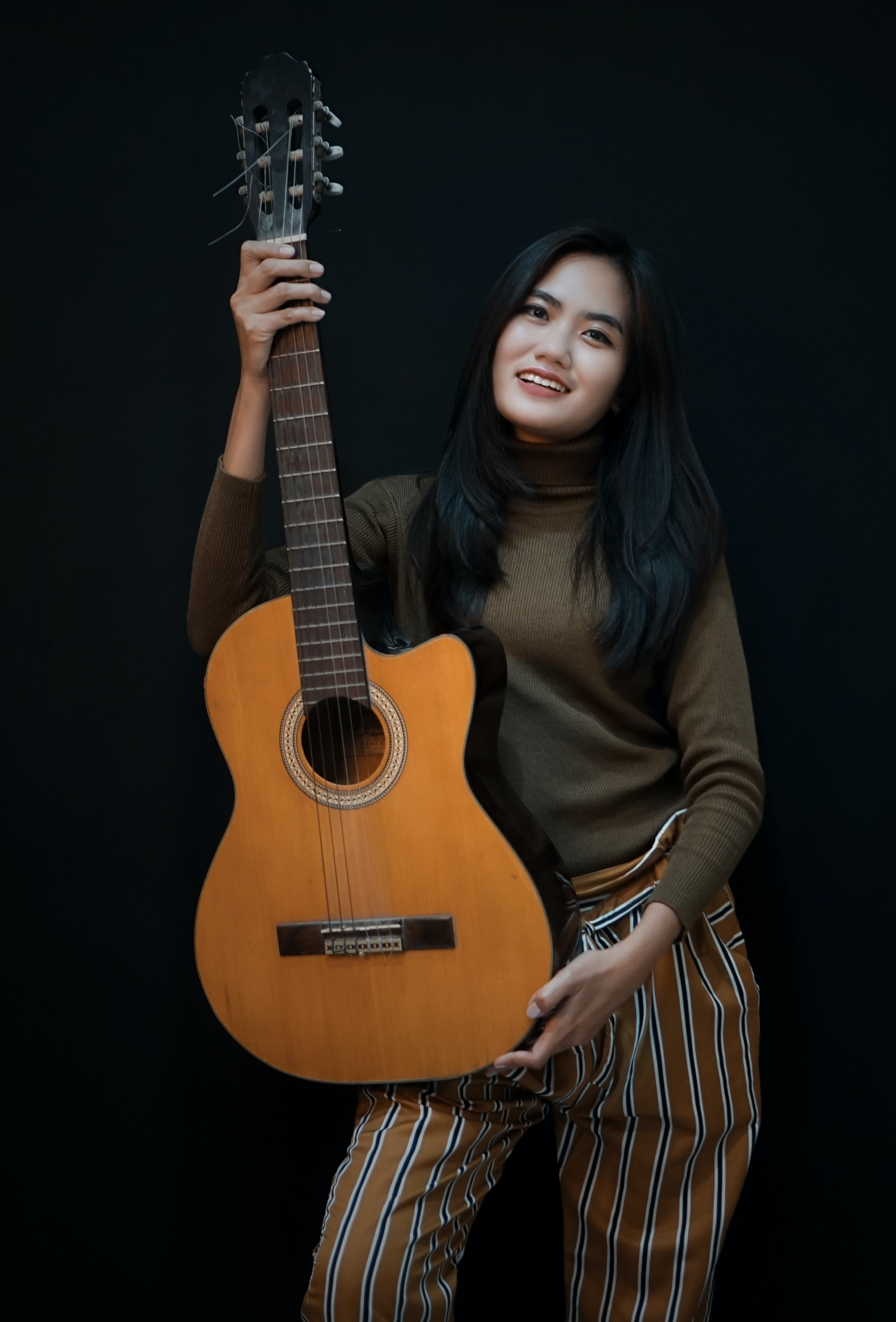 smiling woman while holding cut-away acoustic guitar