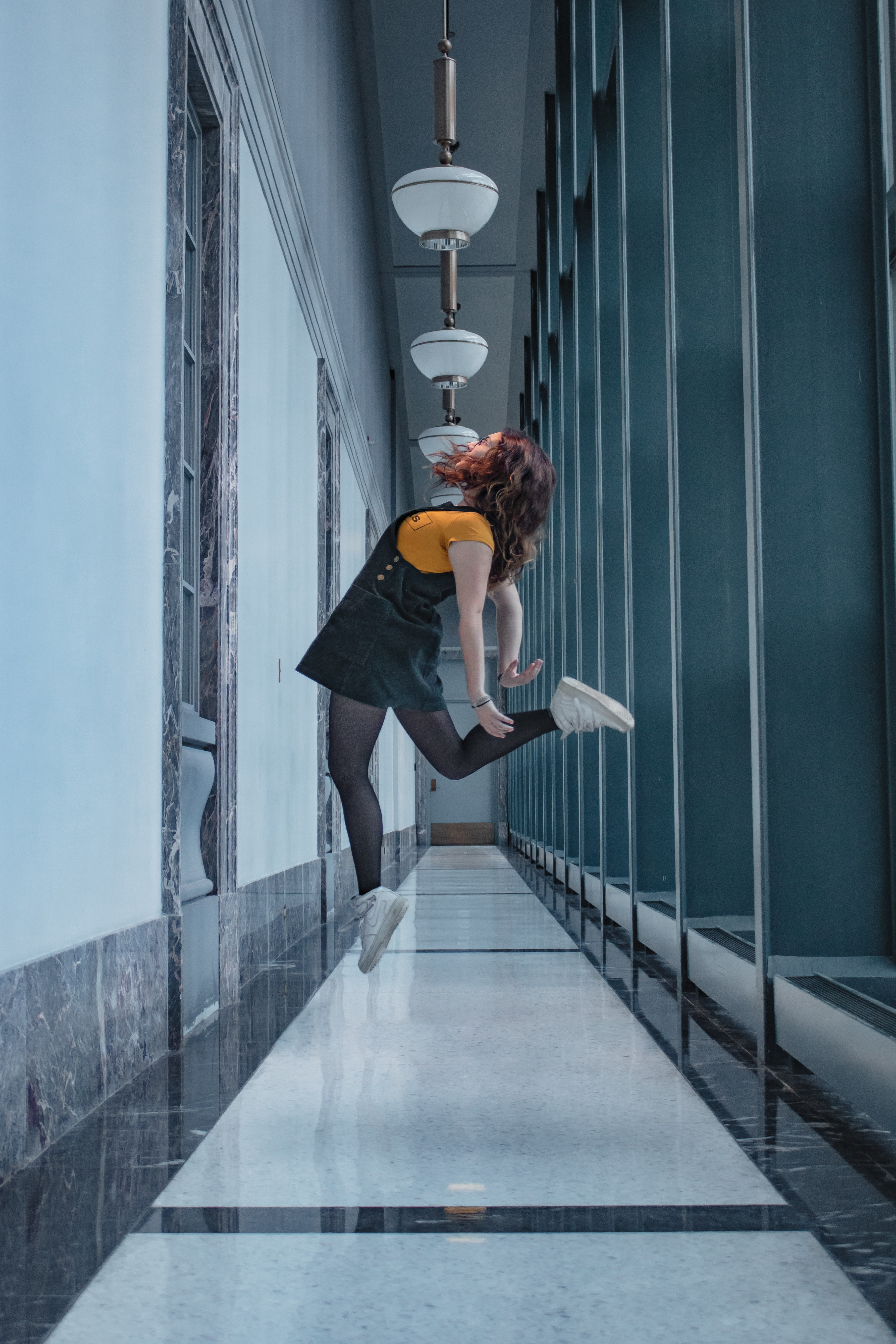 selective color photo of woman jumping in the corridor