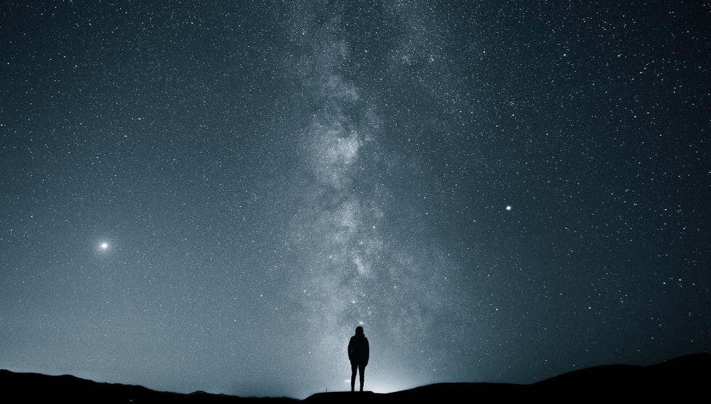 silhouette of person under starry sky
