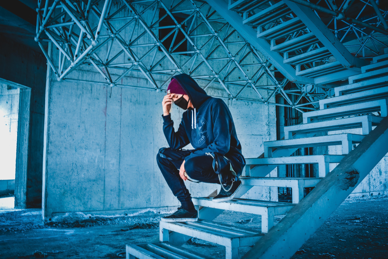 man sitting on white concrete stairs