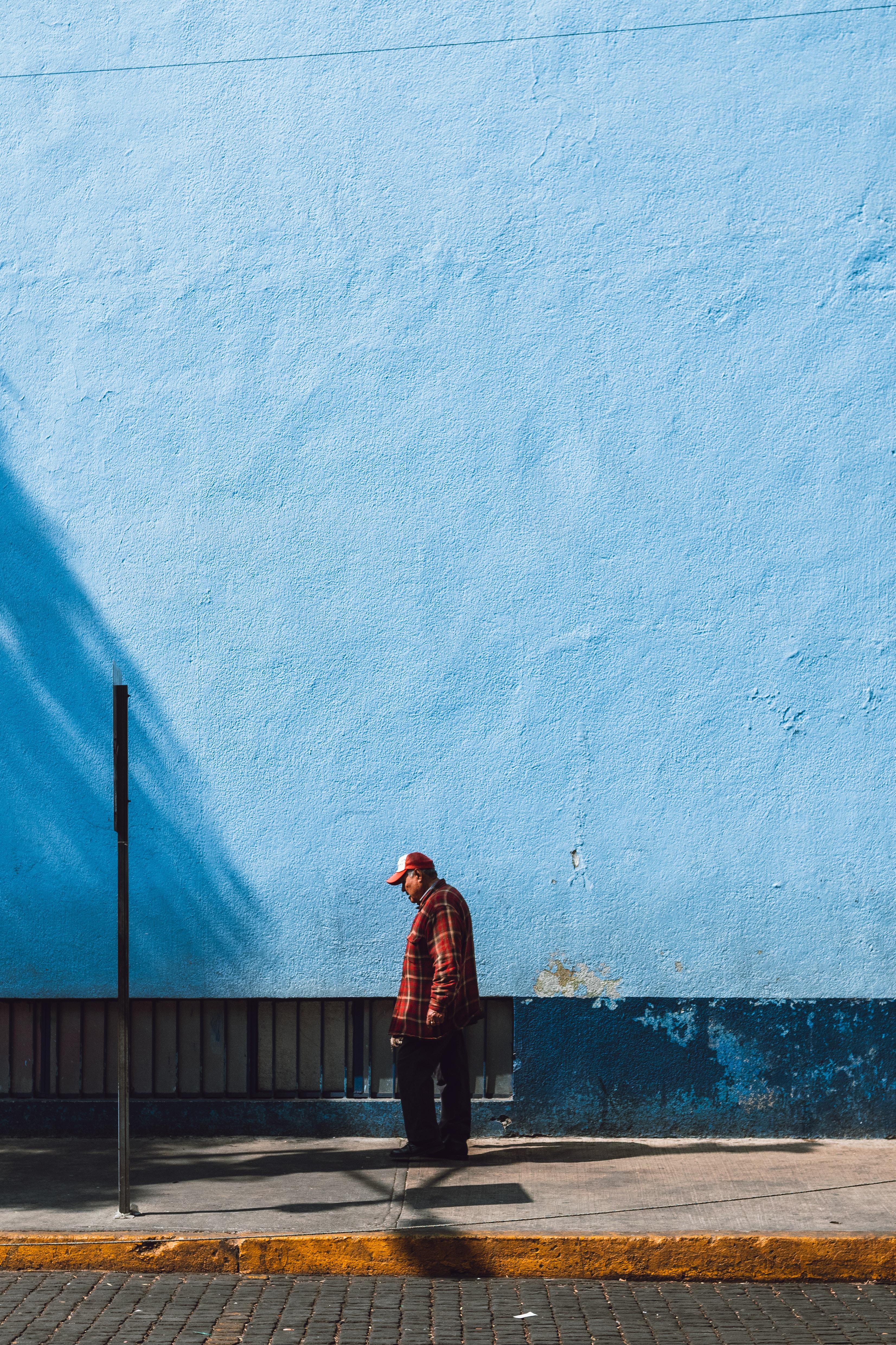 man standing near blue wall