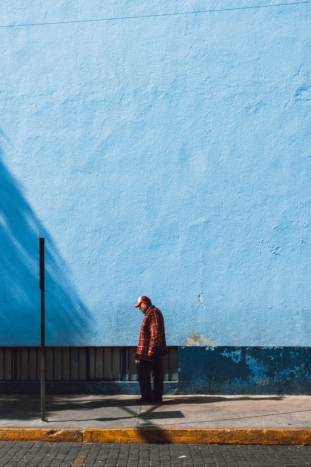 man standing near blue wall