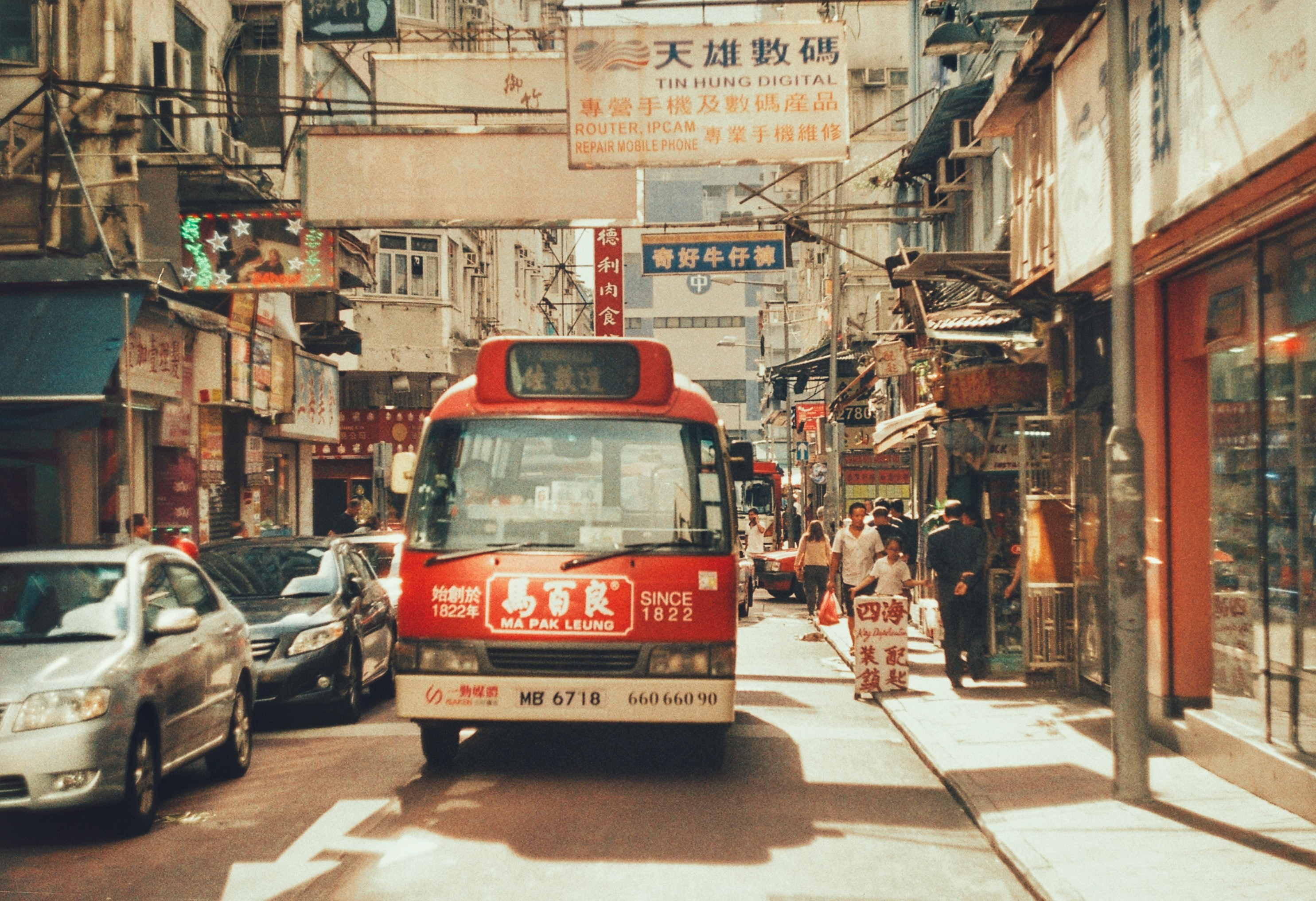 red bus near two cars during daytime