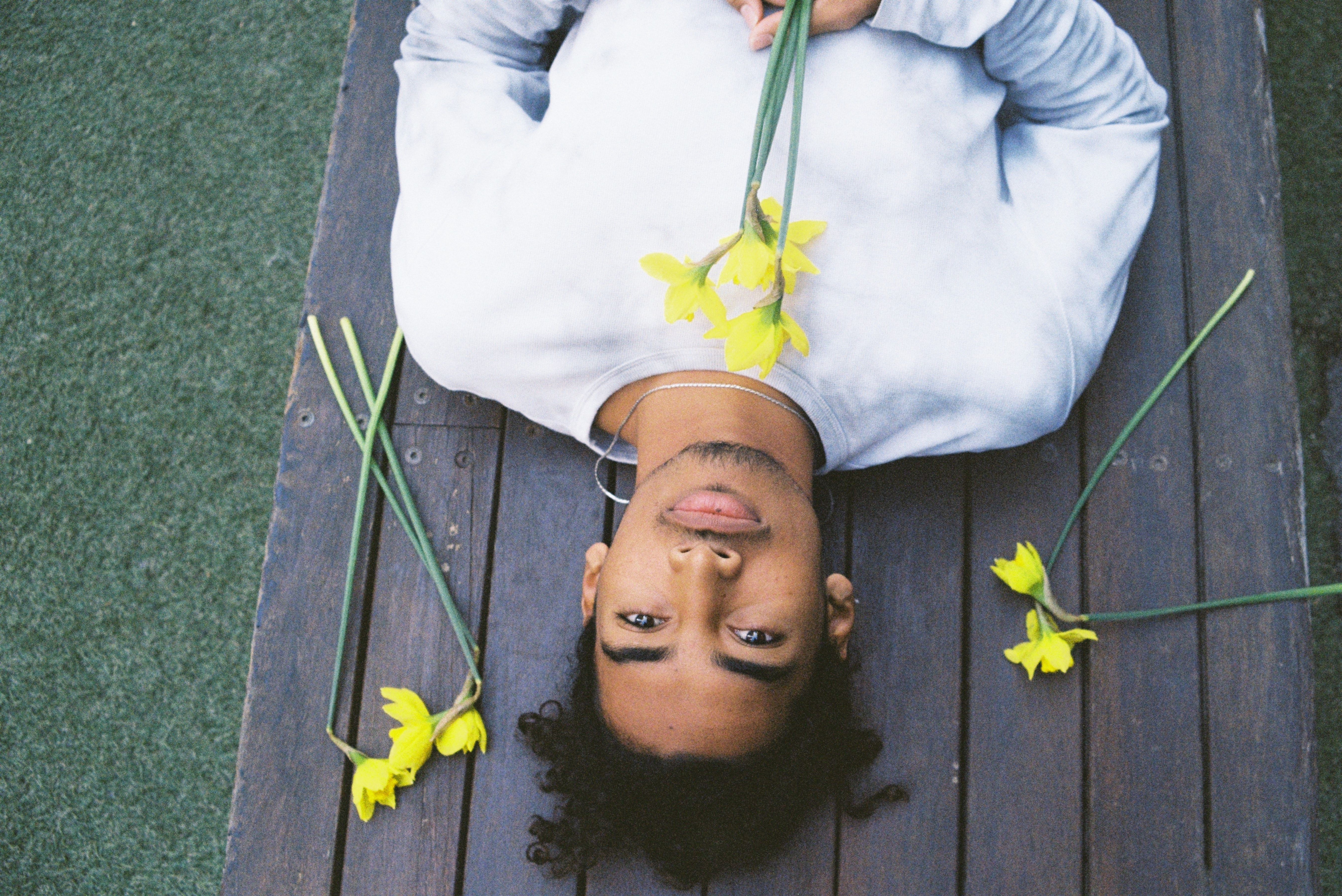 man lying on gray wooden table holding yellow flowers