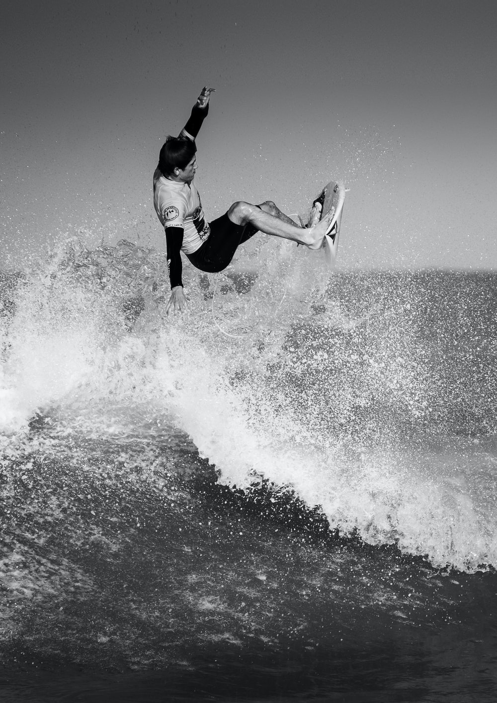 black and white photo of man surfing