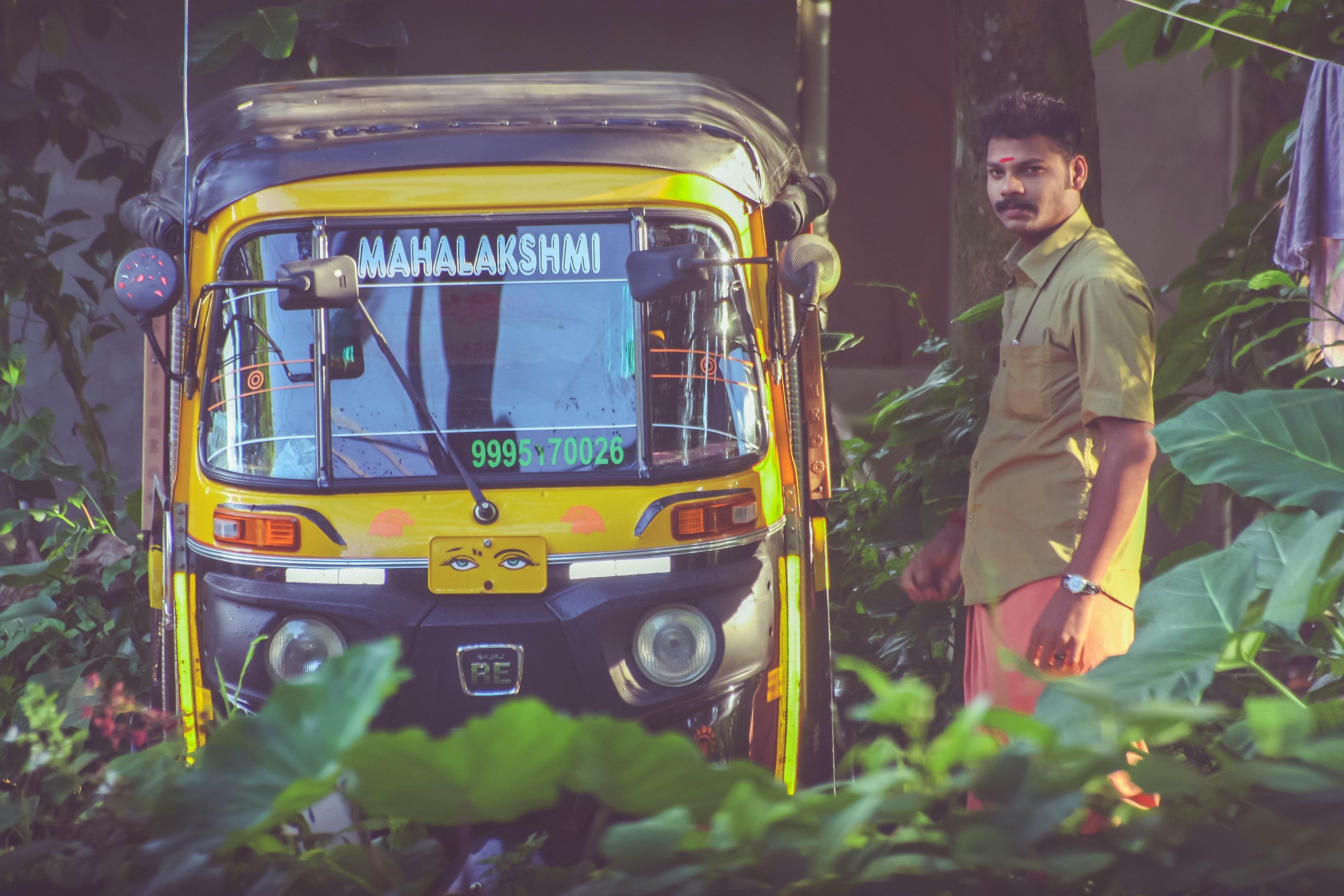 man standing beside of auto-rickshaw