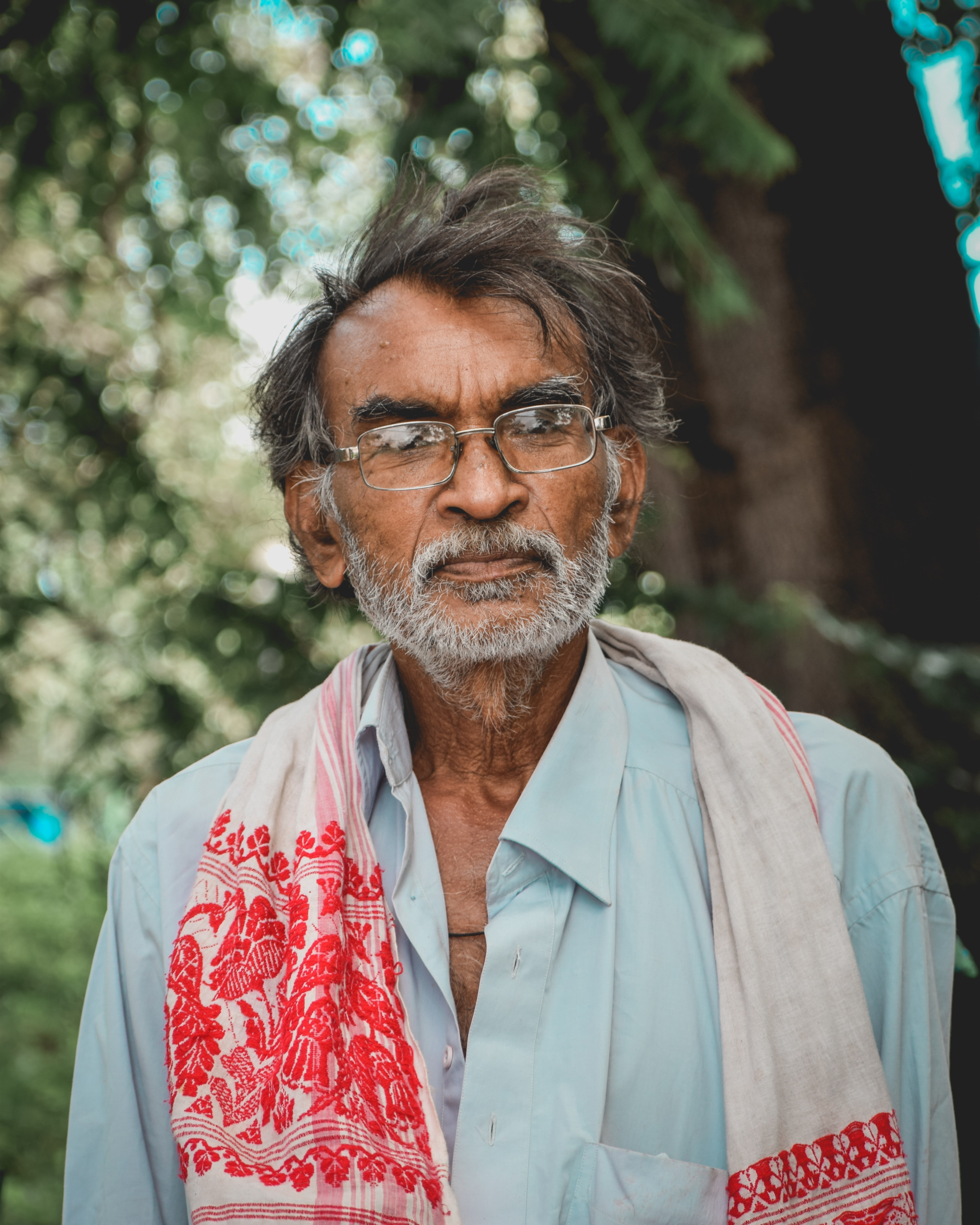 close-up photo of man in white and red floral scarf