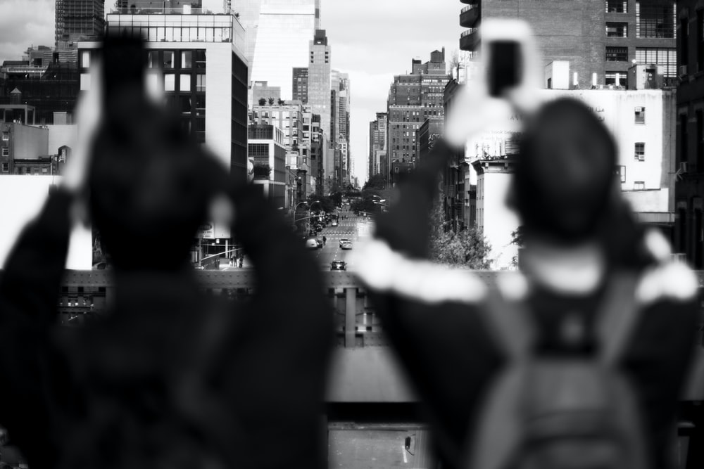 grayscale shot of two persons taking photo of buildings