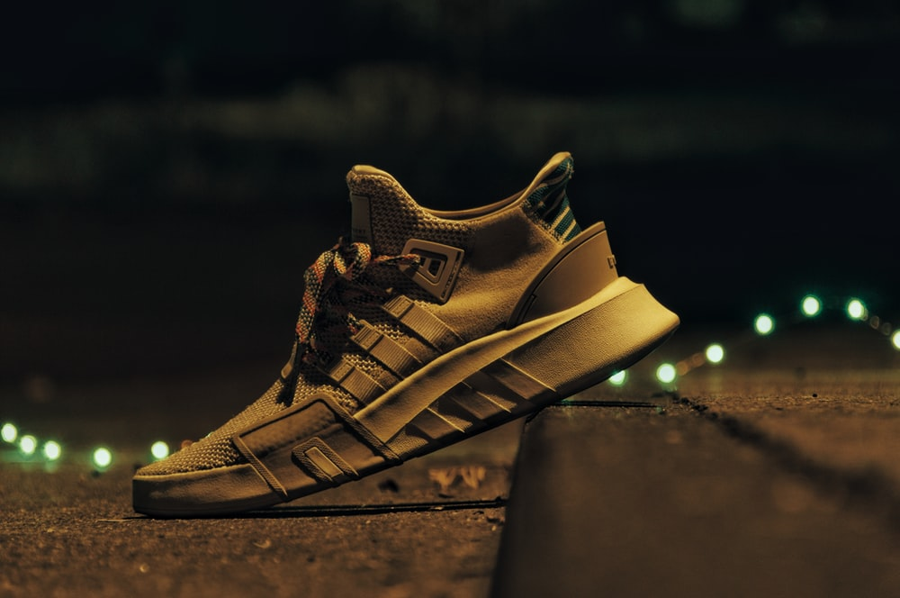 selective focus photo of brown adidas ultra BOOST sneaker on pavement at nighttime