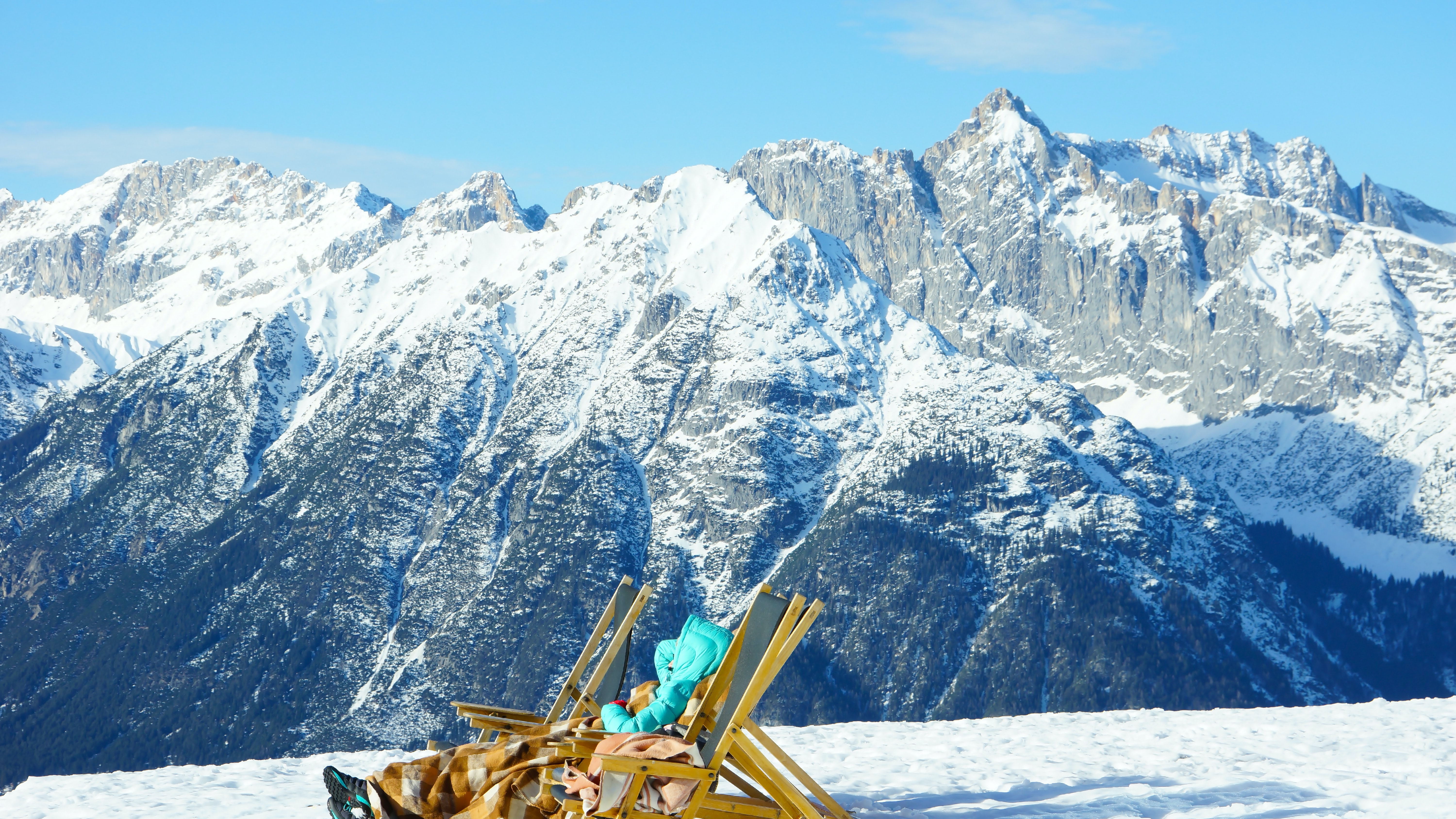 person sitting on adirondack chair on snow mountain