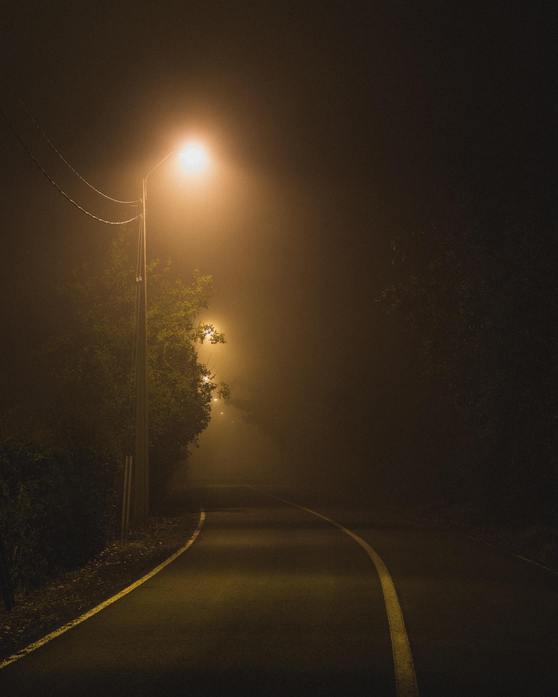 orange street post turned on beside asphalt road during nighttime