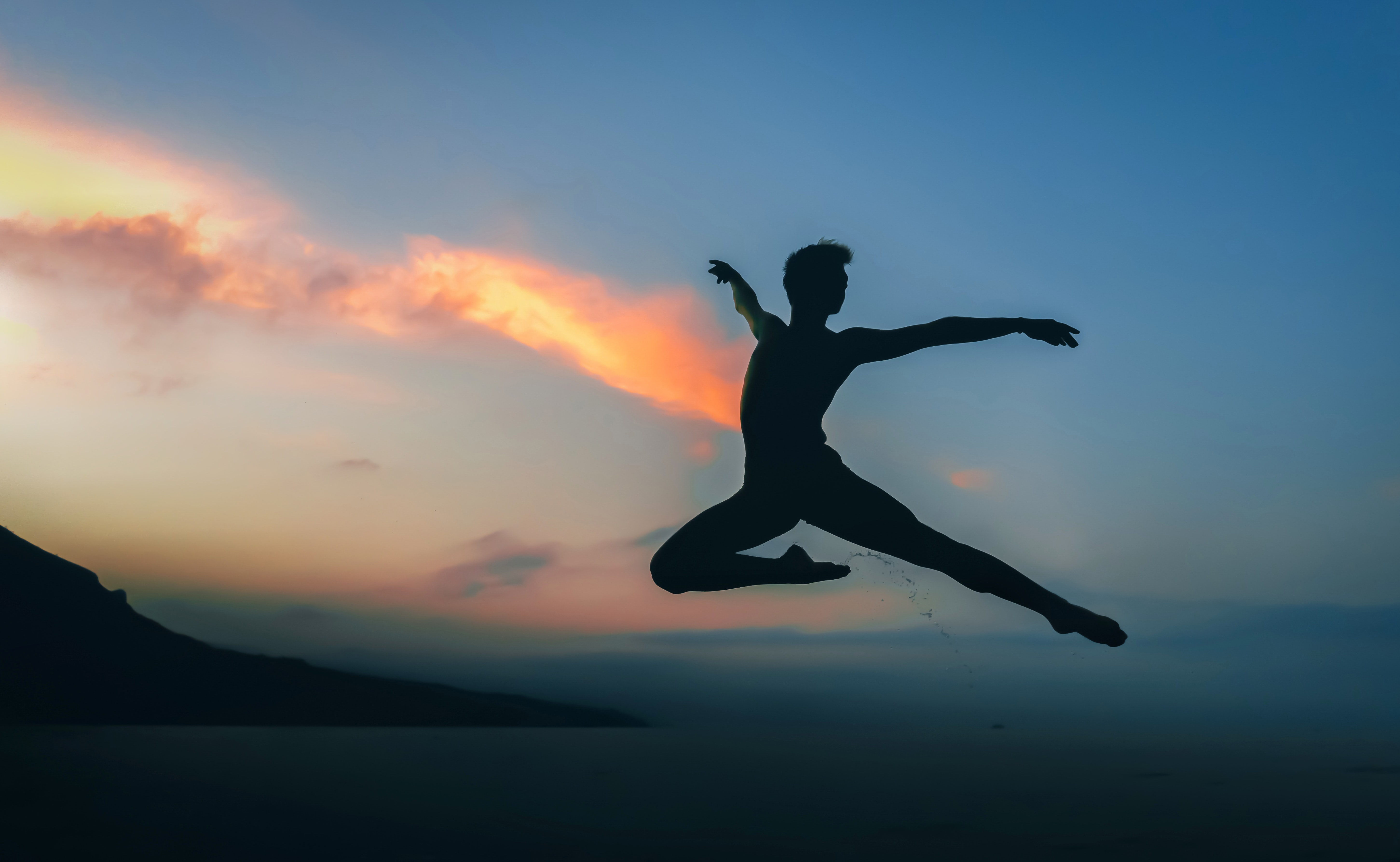 silhouette of man jumping doing ballet dance under golden hour