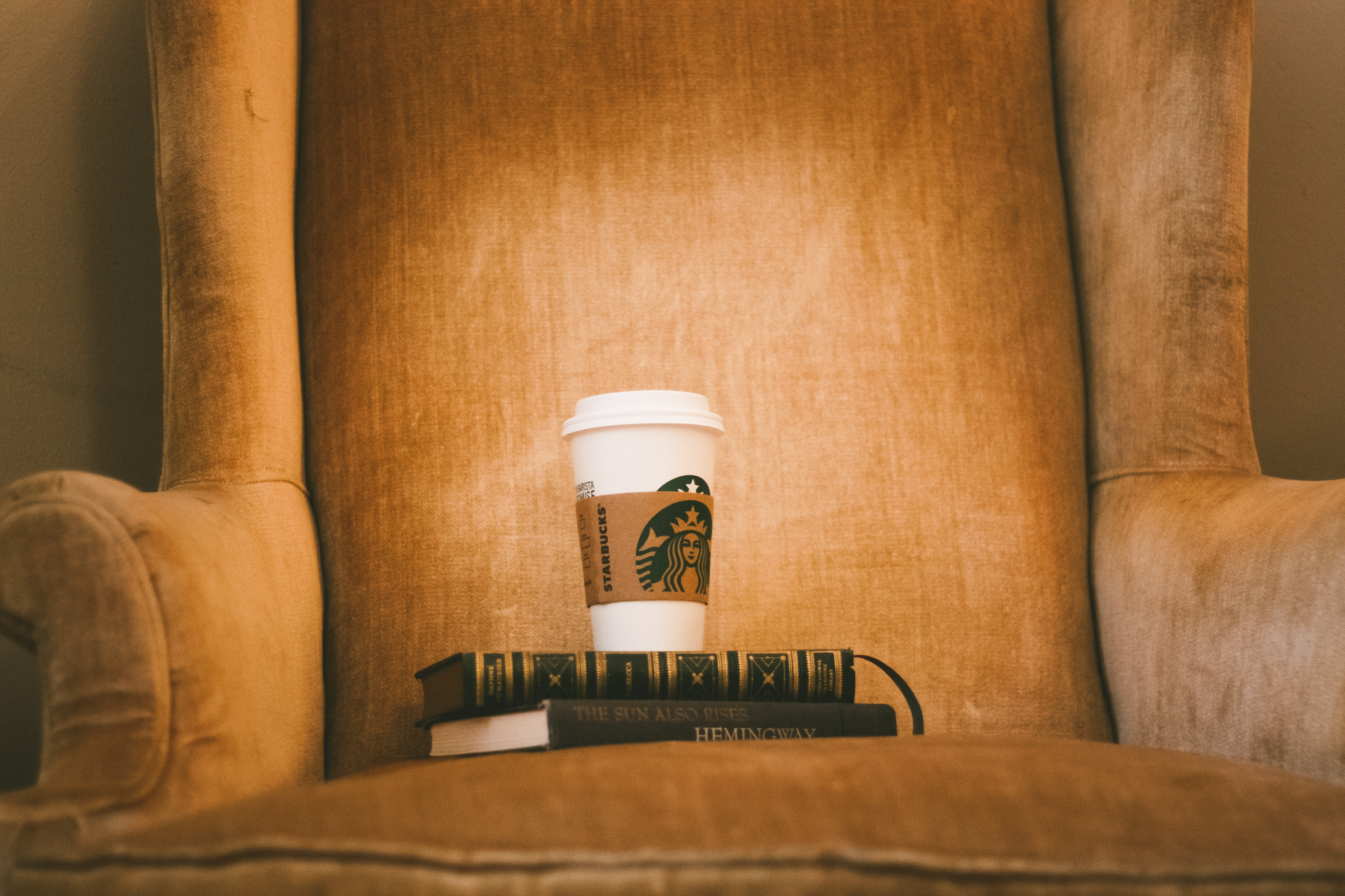white Starbuck plastic cup on brown fabric armchair