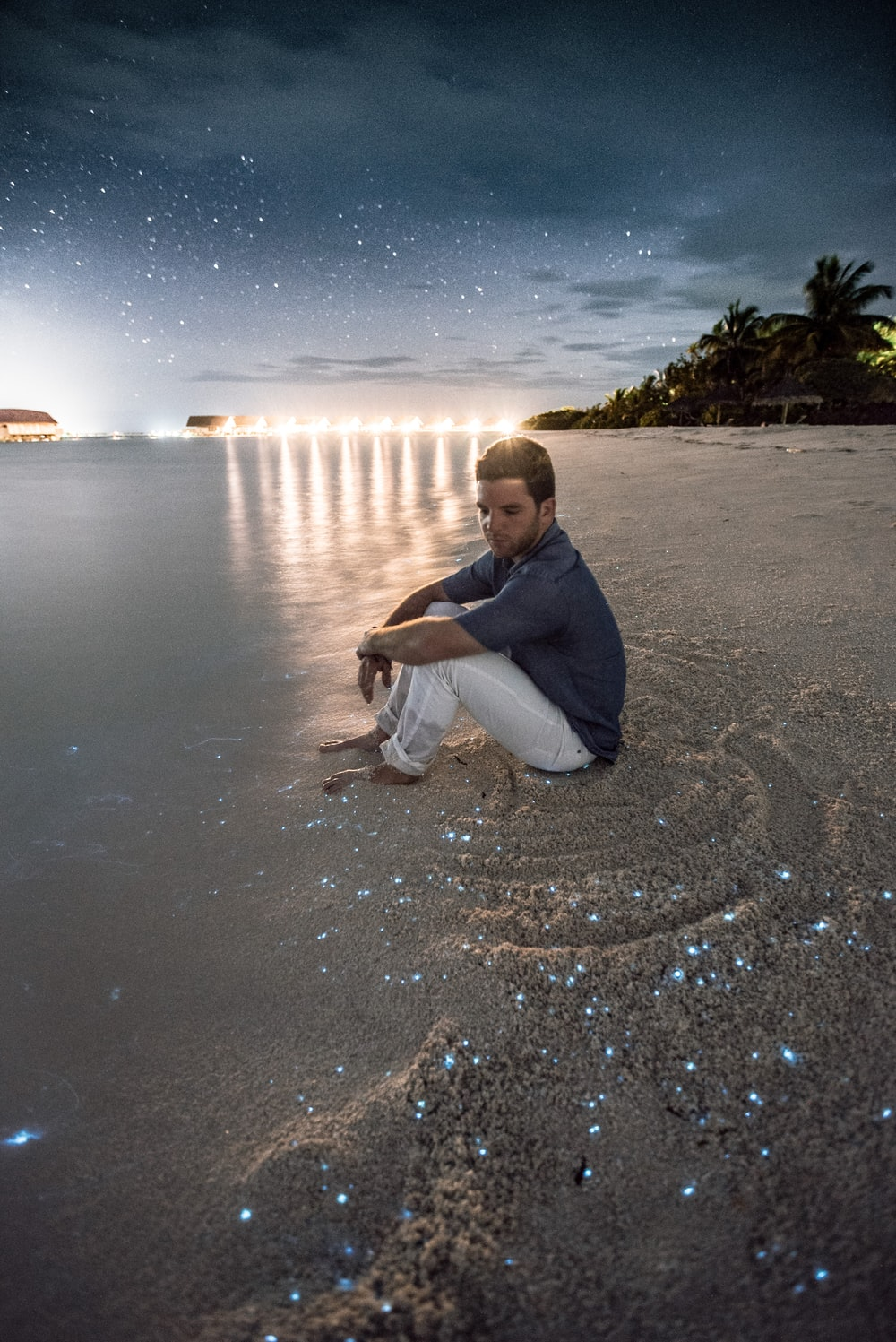 man sitting on brown sand beside body of water