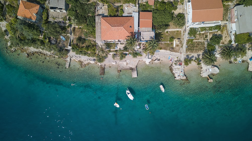 aerial photography of boats on water beside houses
