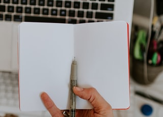person holding book and black pen