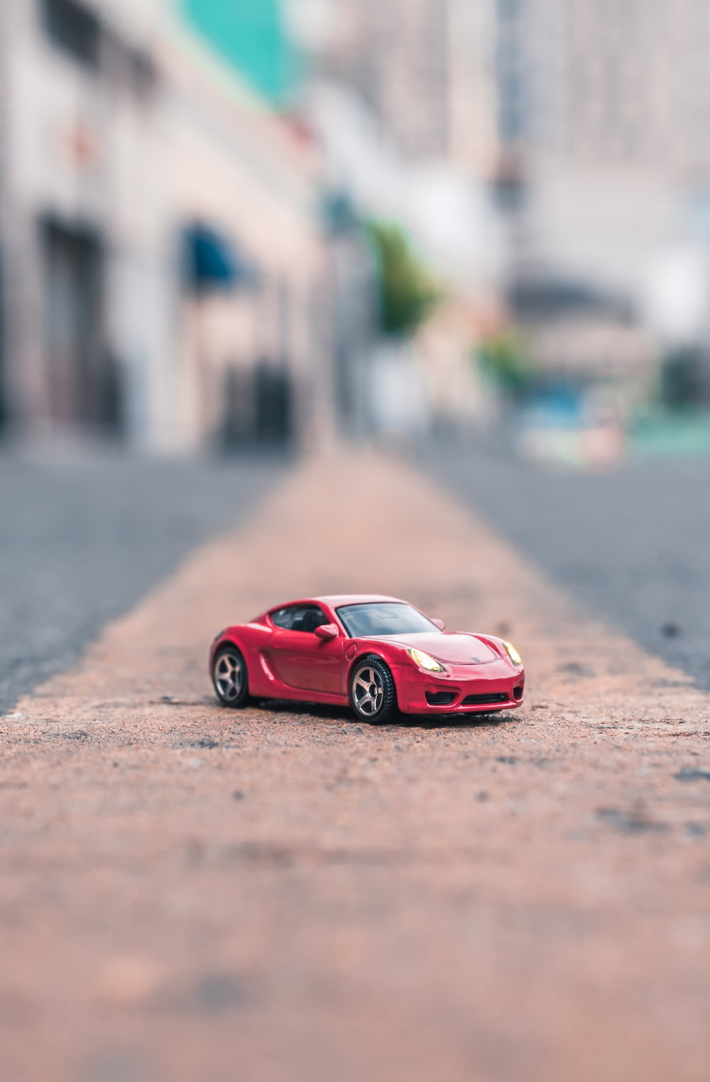 selective focus photography of red coupe scale model on road