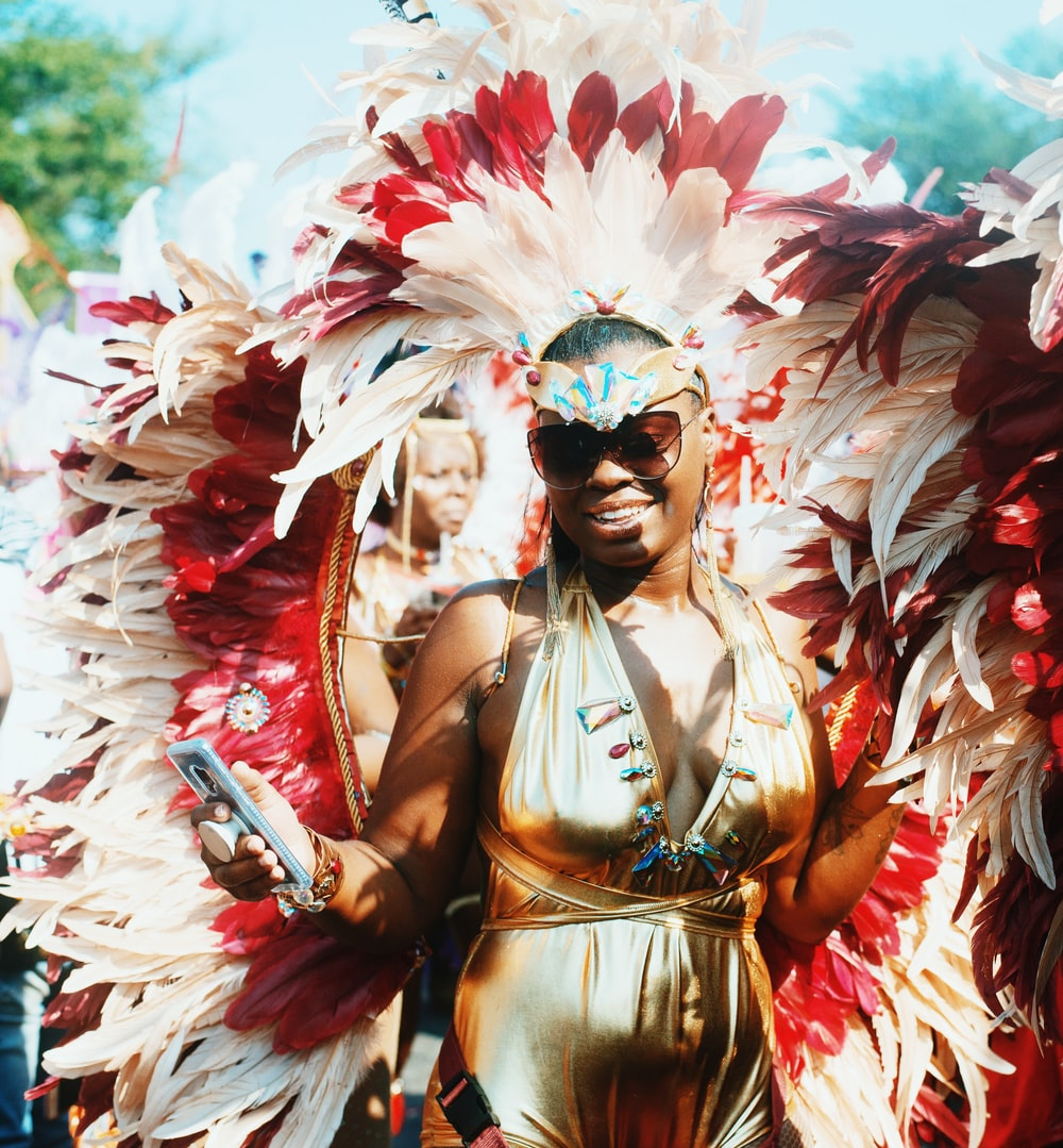 woman in gold halterneck dress walking with people wearing feather headdress