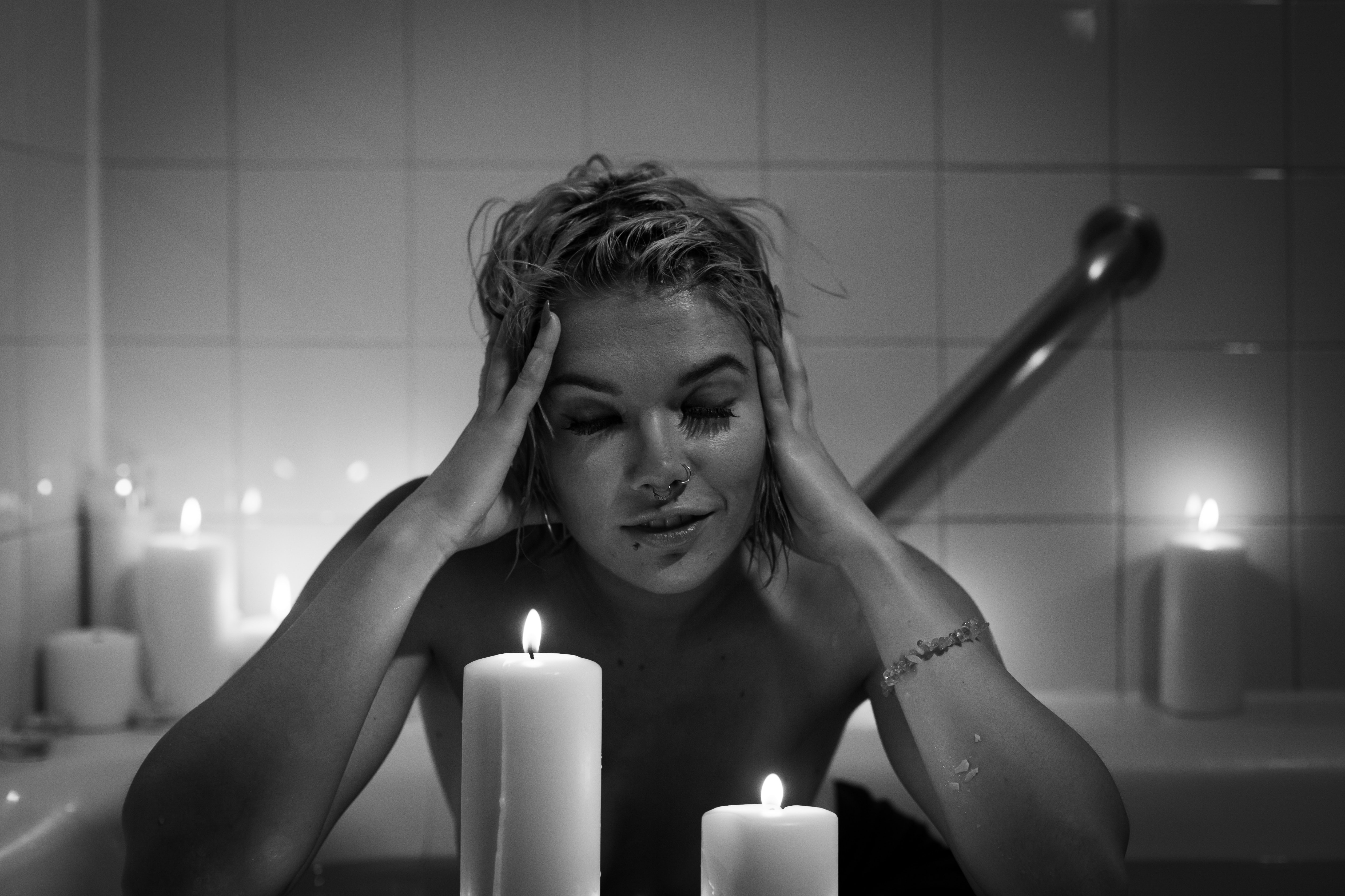 gray scale photography of woman in bathtub in front of pillar candle