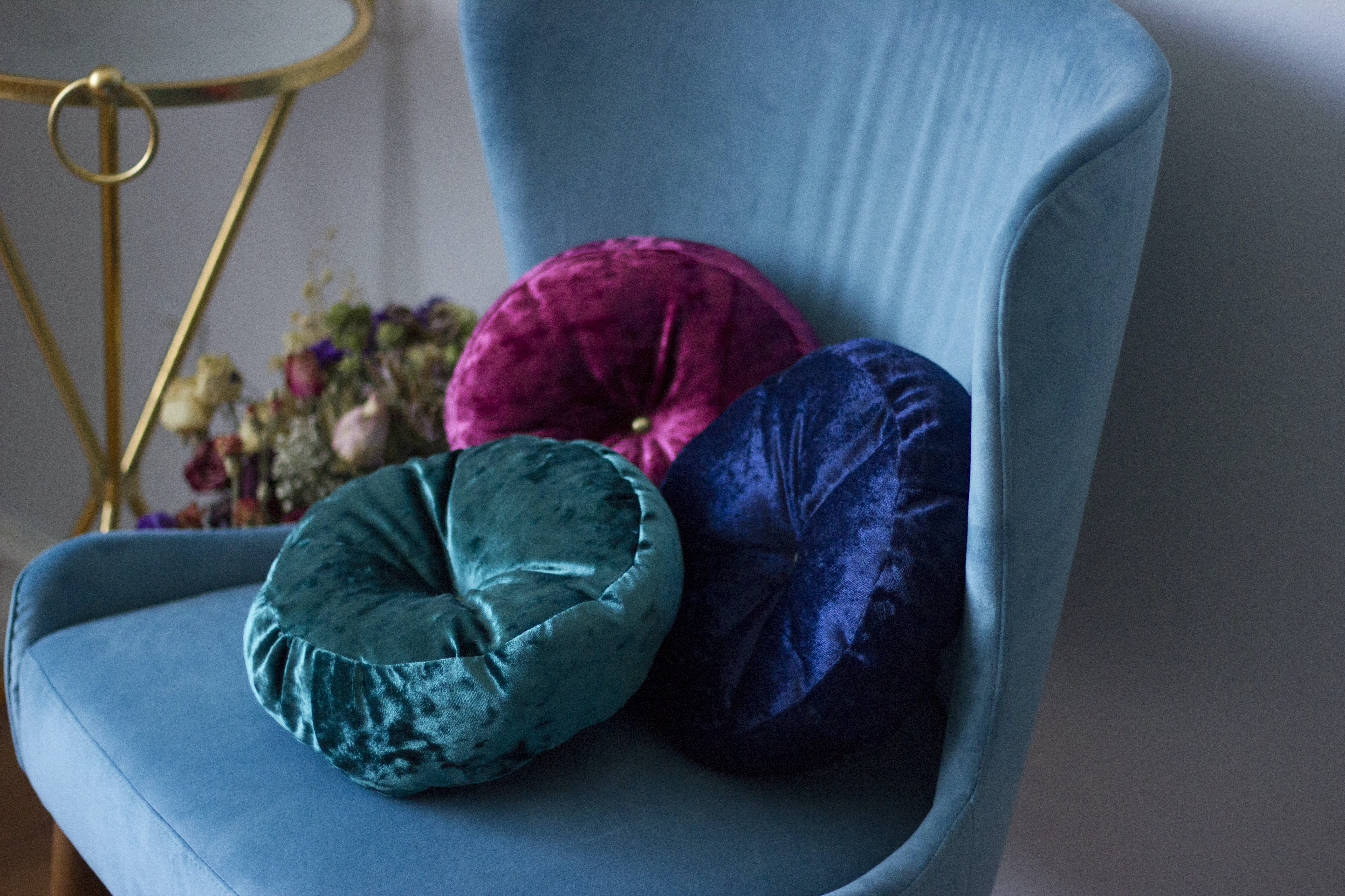three round blue, teal, and pink velvet throw pillows on teal fabric swan chair
