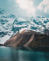 snow capped mountains near body of water at daytime