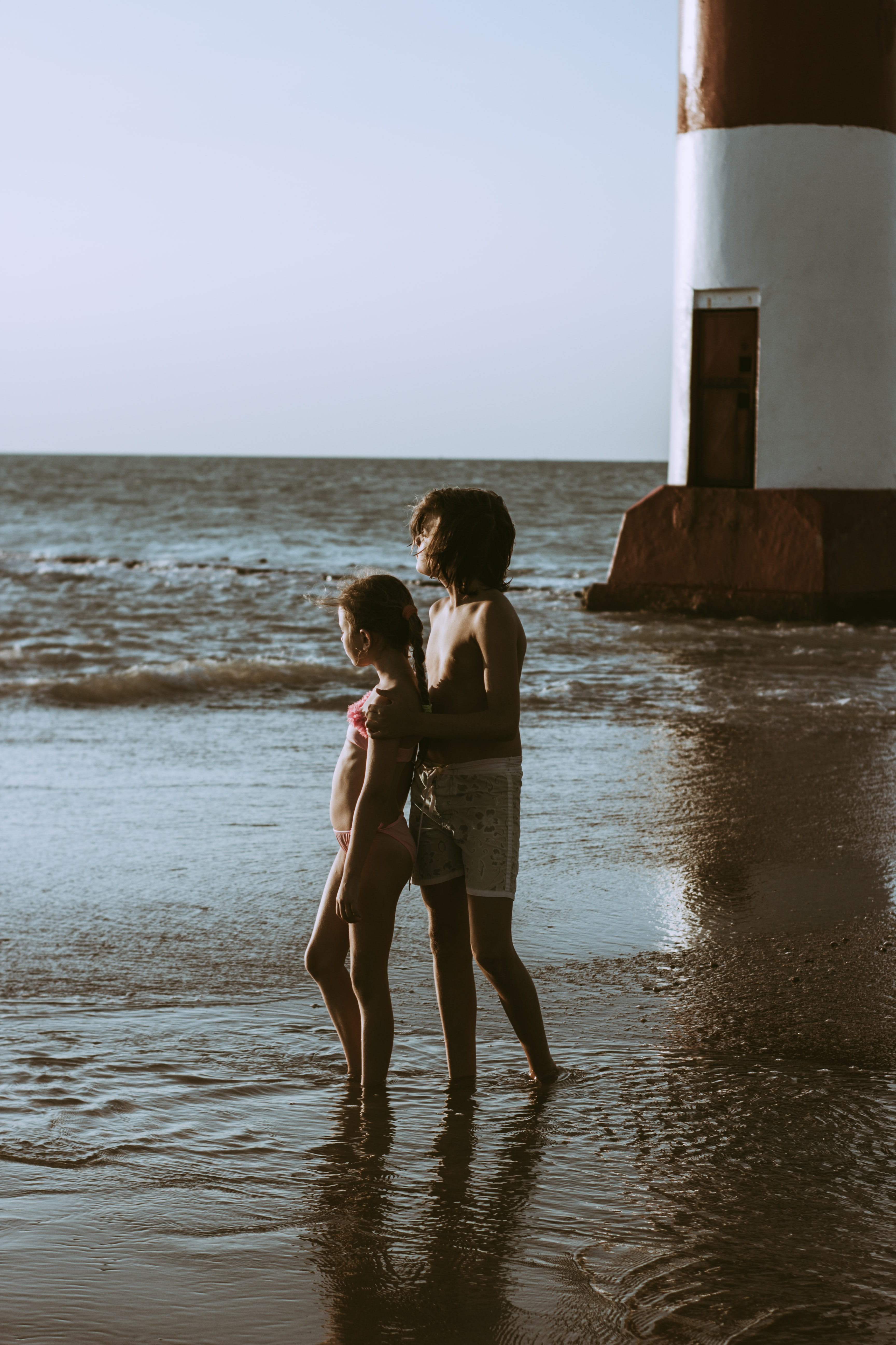 boy and girl standing on near the lighthouse